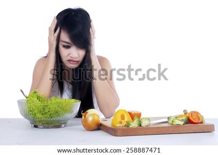 Woman hesitate to eat salad, shot at home  - stock photo