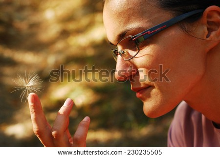 woman holding a thistle seed - stock photo