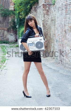 woman holding retro boom box on the street - stock photo
