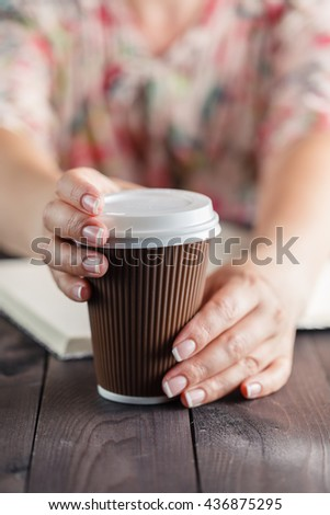 Woman holding takeout coffee at table and opening cup - stock photo