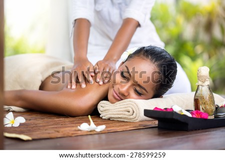 Woman in a day spa getting a deep tissue massage of back  therapy - stock photo