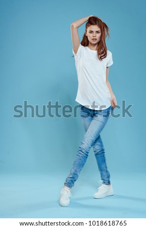 woman in a white T-shirt in jeans in full growth on a blue background