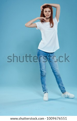 woman in full growth in a white T-shirt on a blue background