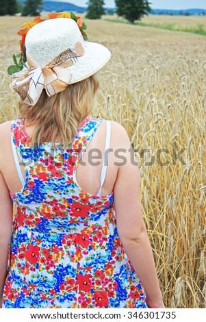Woman in golden wheat field, happy farmer enjoying great harvest. - stock photo