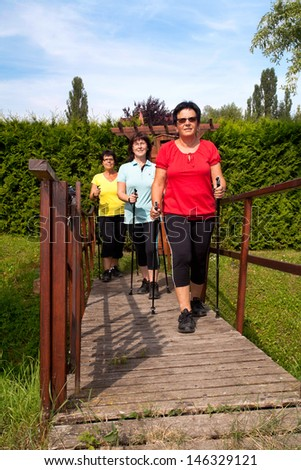 3 woman in nature are nordic Walking in a sports group - stock photo
