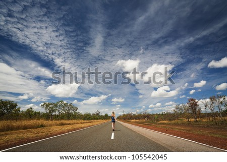 Woman is going through the road of outback vanishing in the desert, Outback Australia,  Northern Territory - stock photo