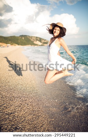 Woman jumping in the air on tropical beach,having fun and celebrating summer,beautiful playful woman in white dress jumping of happiness.Active lifestyle, summer holidays and vacation concept.Freedom - stock photo