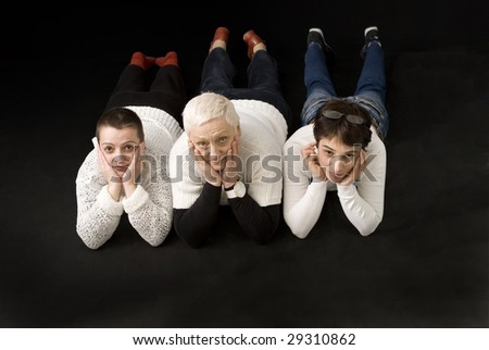 3 woman lying down on black background - stock photo