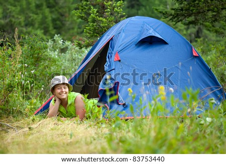woman lying in camp tent and looking at camera - stock photo