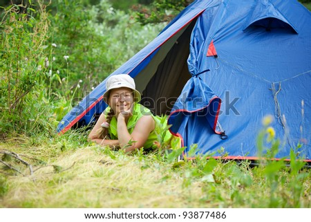 woman lying in camp tent and looking at camera