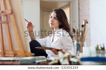 woman paints picture on canvas with oil paints in her studio - stock photo