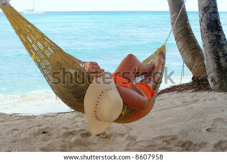 woman relaxing in a hammock on a tropical beach