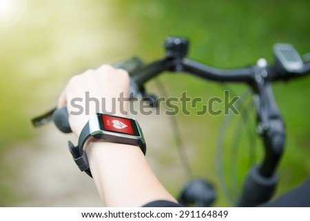 Woman riding a bike with a smartwatch heart rate monitor. Smart watch concept. - stock photo