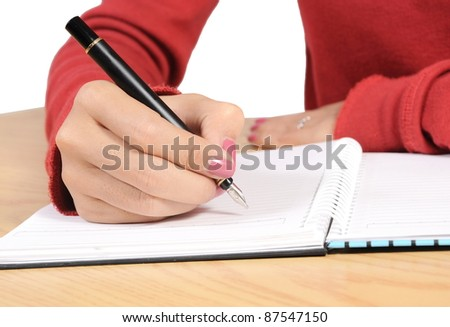 woman's hand writing on a spiral book on the table