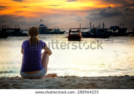 Woman sitting on sea cost and looking in beautiful sunset, back view  - stock photo