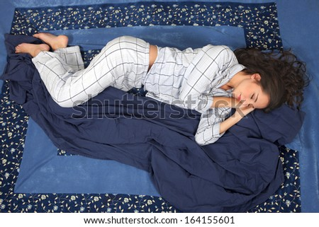 Woman sleeping in side position, in comfort on bed - stock photo