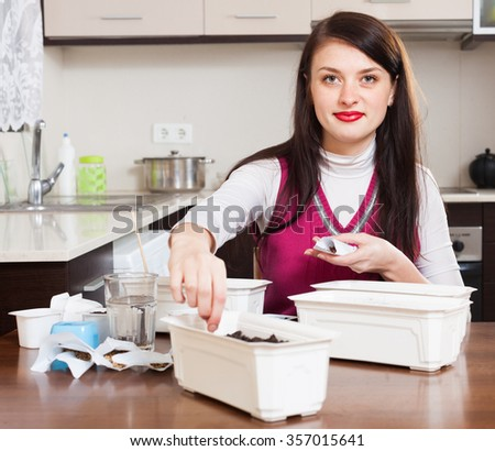 woman sowing seedlings in pots at table in home - stock photo