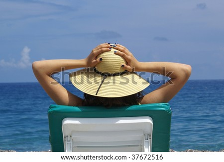 woman sunbathing in a plastic chair on a beautiful beach - stock photo
