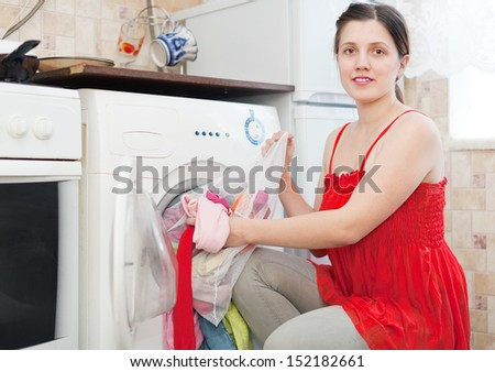 woman using bag for laundry in washing machine at her home