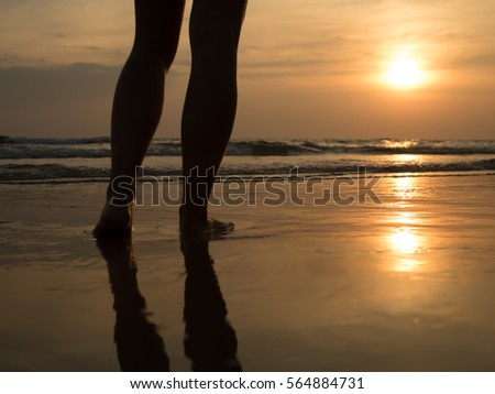 Woman walking on the beach in the sunset