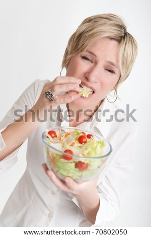 Woman with an unhappy face tasting a salad - stock photo