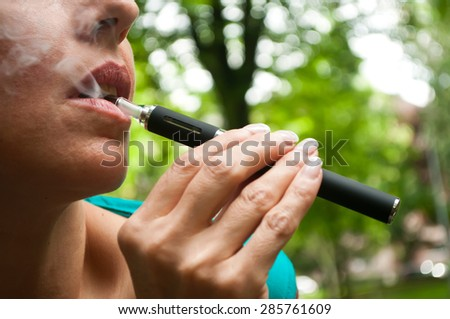 woman  with e-cigarette closeup in outdoor  - stock photo