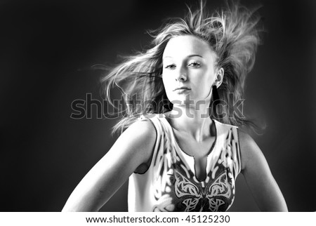 Woman with hair billowing on black background - stock photo