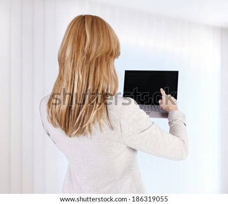 Woman with laptop from a back - stock photo
