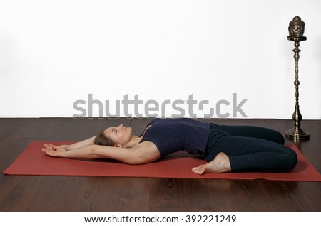 women are yoga exercises at home. She is lying on a red yoga Mat in the back. Legs bent to the hips. Arms stretched up - stock photo