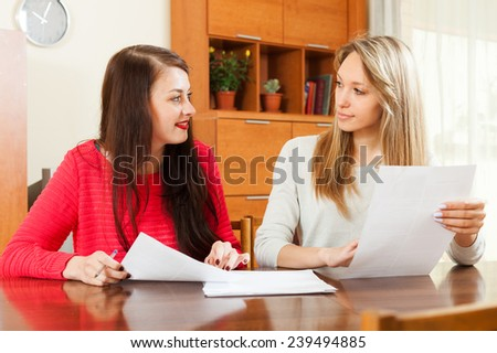 women looking  documents at table in home or office interior