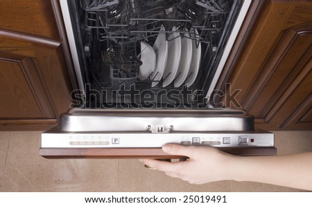 Women's hand closes filled dishwasher - stock photo