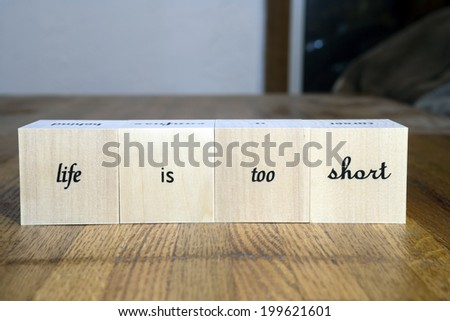 Wood blocks with words that say life is too short. - stock photo