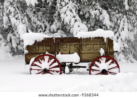 Wood wagon outside of a home in the snow - stock photo