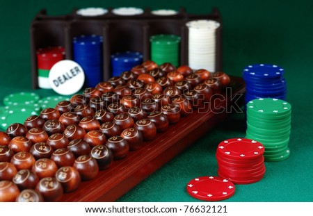 wooden  bingo balls, stack of Poker chips and dealer button on a green background.Focus on ball 54 - stock photo