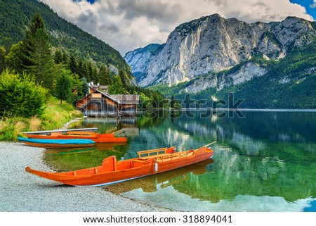 Wooden boat dock with traditional boats and high rocky mountains in background,Altaussee,Salzkammergut,Austria,Europe - stock photo