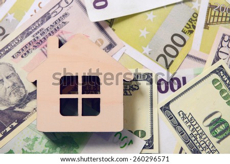 wooden house on a background of banknotes - stock photo