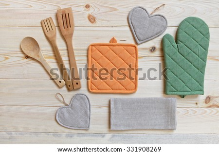 Wooden kitchen utensils,potholder, glove and napkin on wooden table,top view