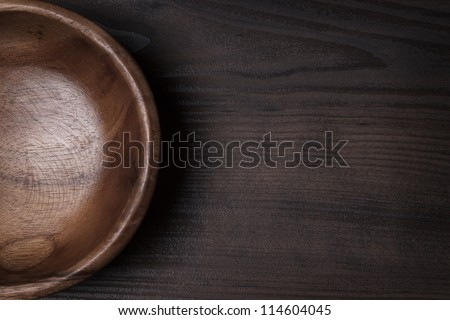 wooden salad bowl on the brown table - stock photo