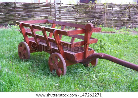 wooden wheelbarrow on a green field - stock photo
