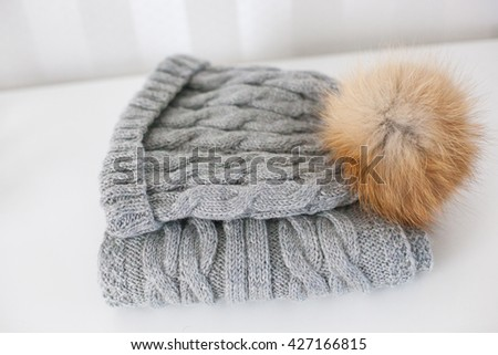 Wool winter hat, scarf on the white table - stock photo