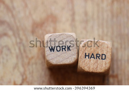 """""""Work hard"""" printed on two wood dice against wood background open for copy - stock photo"""