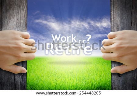 """Work or Retire"" Motivational quotes. Hands opening a wooden door then found a texts floating among new world as green grass field, Blue sky and the Sunrise. - stock photo"