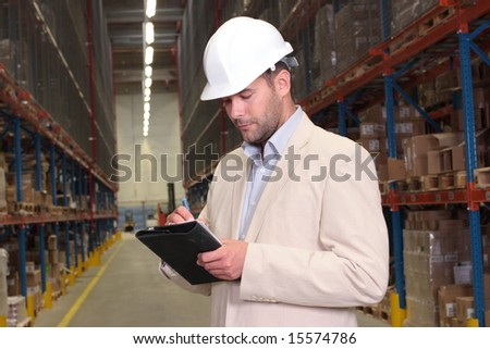 worker counting stocks and making notes - stock photo