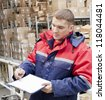 worker in the winter coats on indoor unheated stock status maintains documentation and sorting incoming goods     warehouse worker in a special uniform  is recording and accounting - stock photo