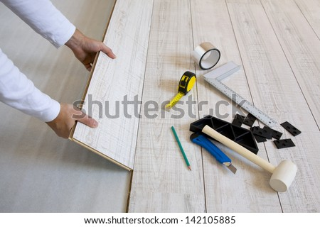Worker laying a floor with laminated flooring boards - stock photo