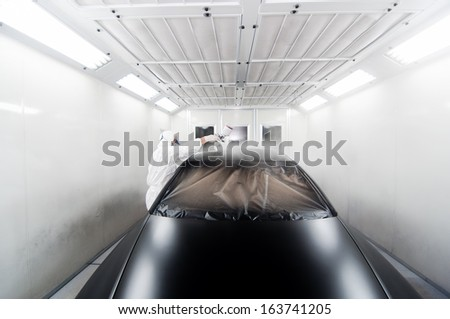 worker painting a black car in a special garage, wearing a white costume and protective gear - stock photo