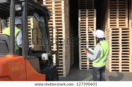 workers  at unloading works with forklift loader in warehouse - stock photo