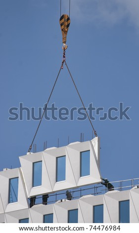 Workers positioning a hoisted prefab facade element - stock photo
