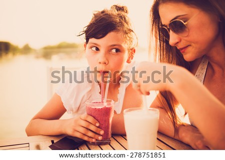 Worried and tired mother drinking juice with her daughter at cafe. Leave your work problems at work, don't affect your child with them - stock photo