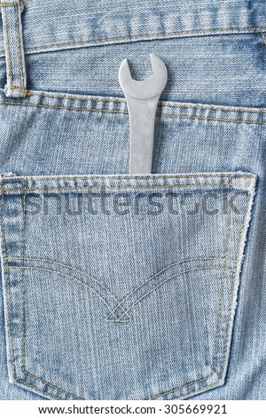 wrench in a jeans pocket. Close up. - stock photo